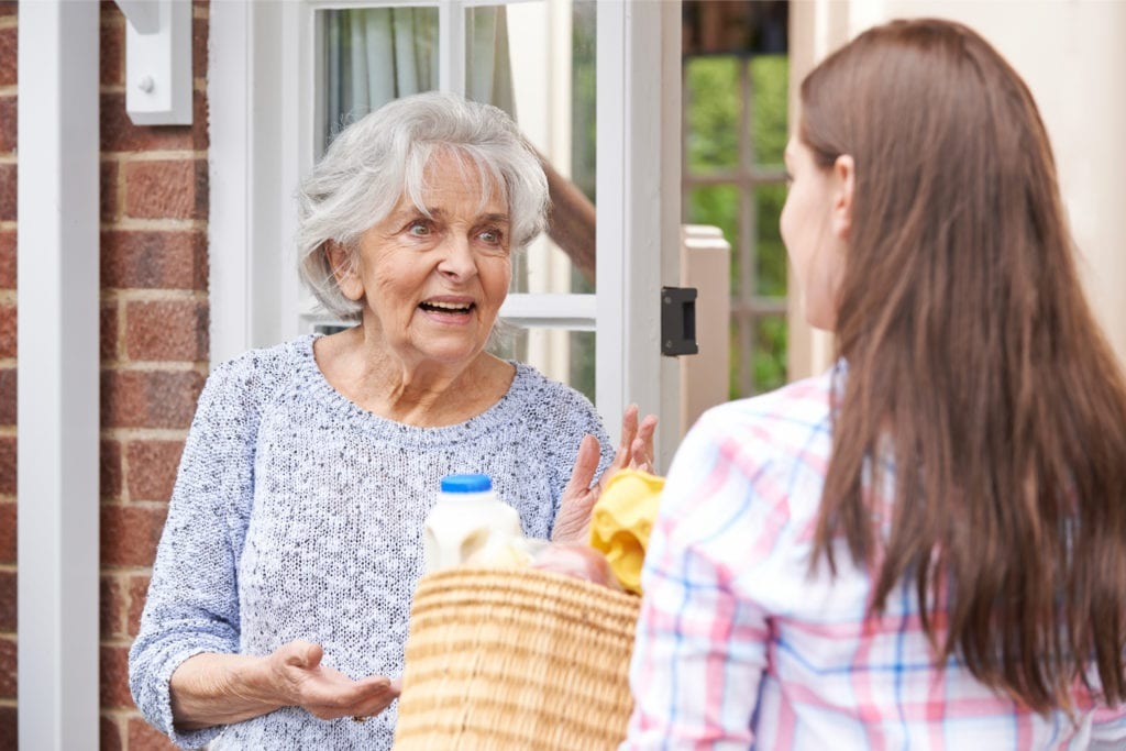 A young woman bringing groceries to an elderly woman